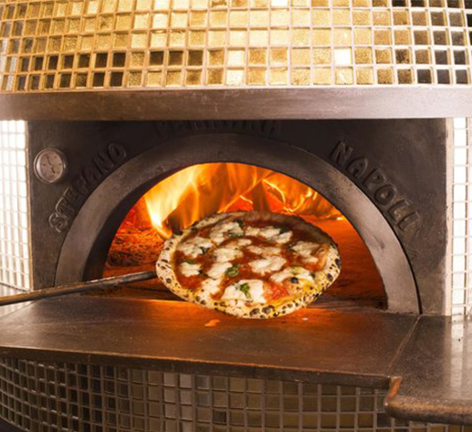 Pizza coming out of wood oven